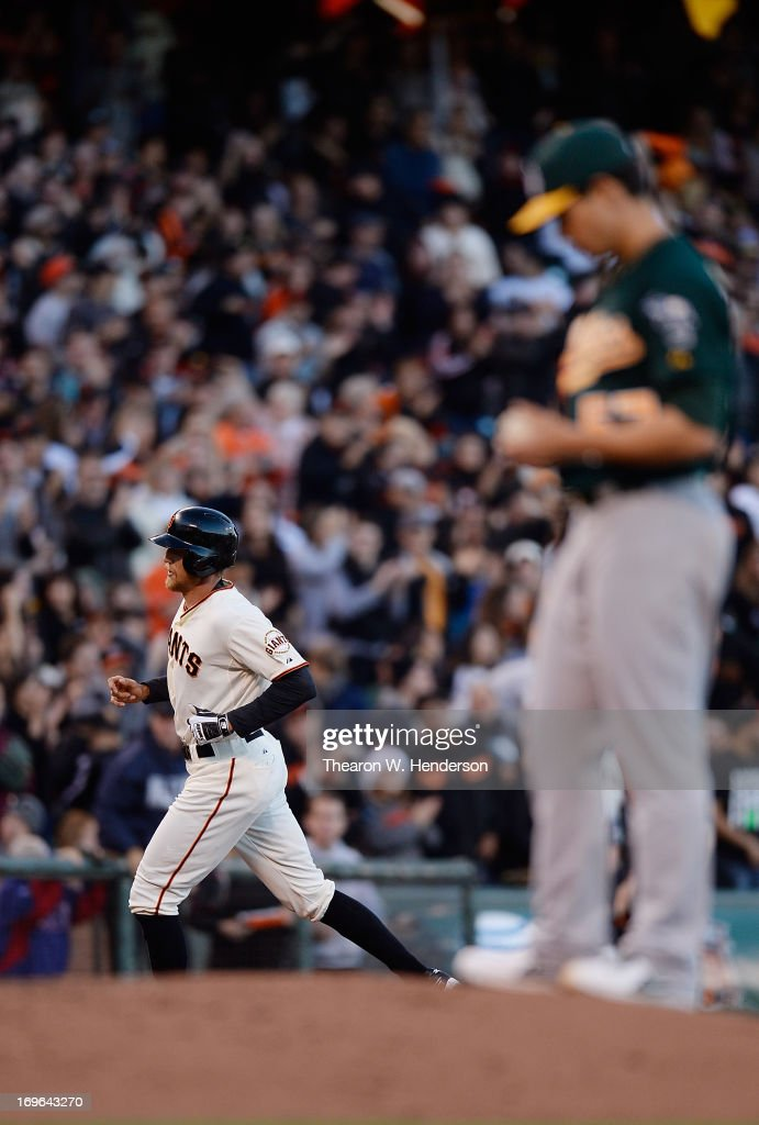 <a gi-track='captionPersonalityLinkClicked' href=/galleries/search?phrase=Hunter+Pence&family=editorial&specificpeople=757341 ng-click='$event.stopPropagation()'>Hunter Pence</a> #8 of the San Francisco Giants trots around the bases after hitting a solo home run as pitcher <a gi-track='captionPersonalityLinkClicked' href=/galleries/search?phrase=Tommy+Milone&family=editorial&specificpeople=8240408 ng-click='$event.stopPropagation()'>Tommy Milone</a> #57 of the Oakland Athletics looks on in the second inning at AT&T Park on May 29, 2013 in San Francisco, California.