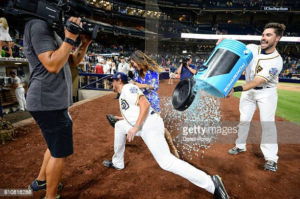 Hunter Renfroe of the San Diego Padres center dodges a cooler dumped on him by Austin Hedges after a baseball game against the Los Angeles Dodgers at...