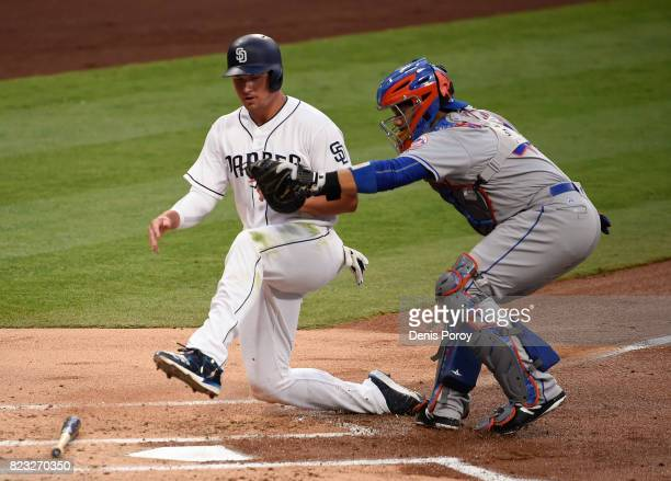 Hunter Renfroe of the San Diego Padres is tagged out at the plate by Rene Rivera of the New York Mets during the first inning of a baseball game at...