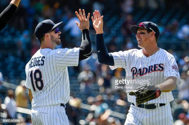 Hunter Renfroe of the San Diego Padres right highfives Austin Hedges after beating the Cincinnati Reds 42 in a baseball game at PETCO Park on June 14...