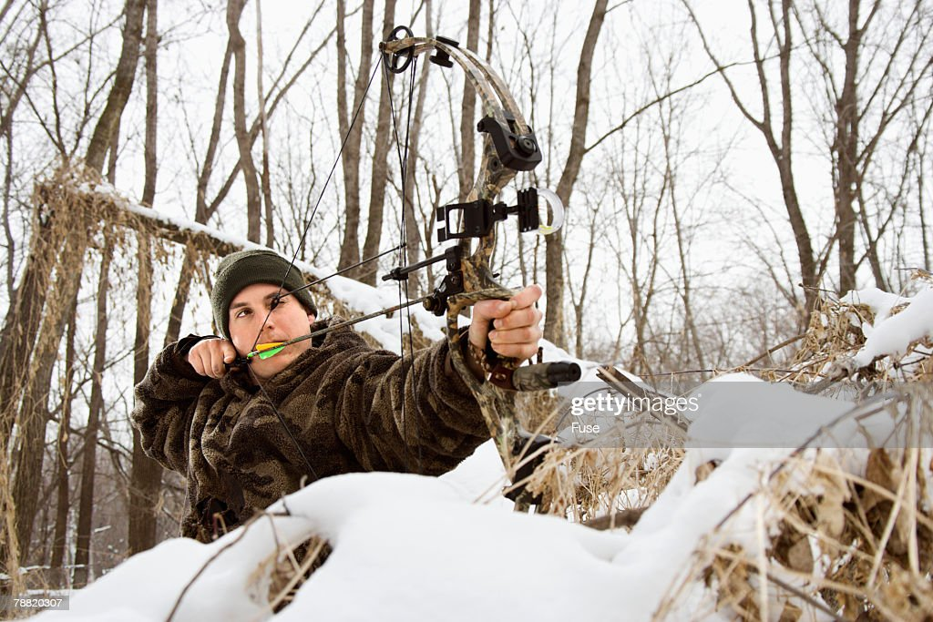 Hunter Shooting Bow and Arrow in Snow