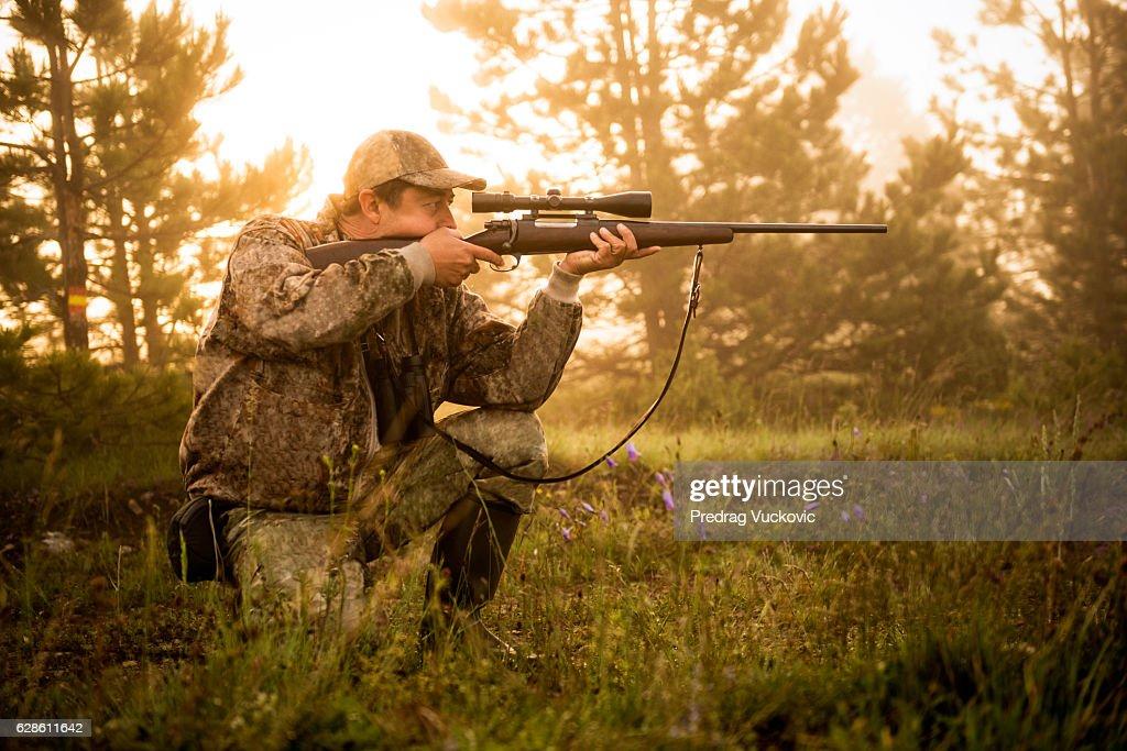 Hunter shooting with rifle : Stock Photo