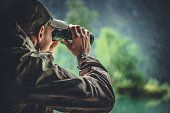 Caucasian Hunter in Masking Camouflage Uniform with Binoculars. Hunter Spotting Game. Poacher or Soldier Clothing.