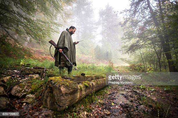 Hunter standing on fallen tree