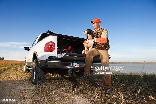 Hunter with dog sitting on truck