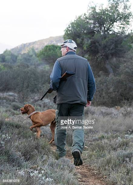 Hunter with his shotgun and hunting dog