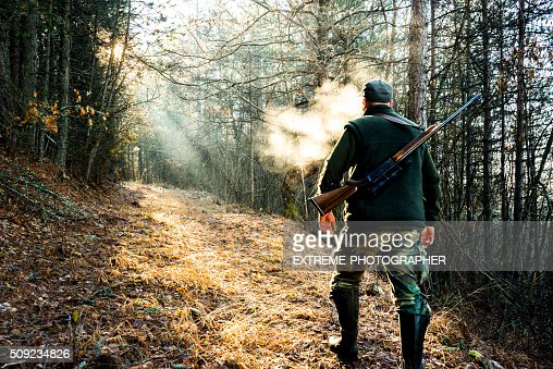 Hunter with rifle walking in the forest