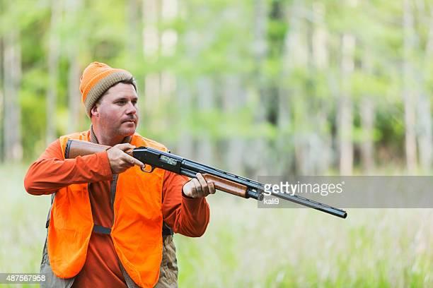 Hunter with shotgun in field near woods