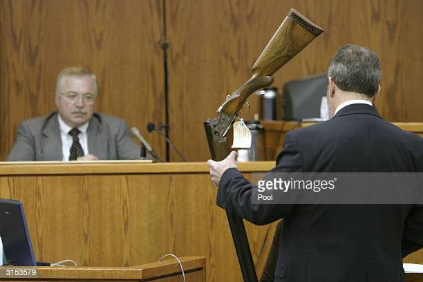 Hunterdon County Assistant Prosecutor Steven Lember holds up the Browning Citori shotgun used in the fatal shooting of limo driver Costas 'Gus'...