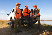 Hunters sitting on tailgate of truck