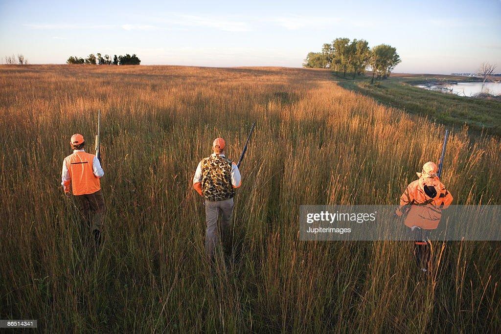 Hunters walking through field