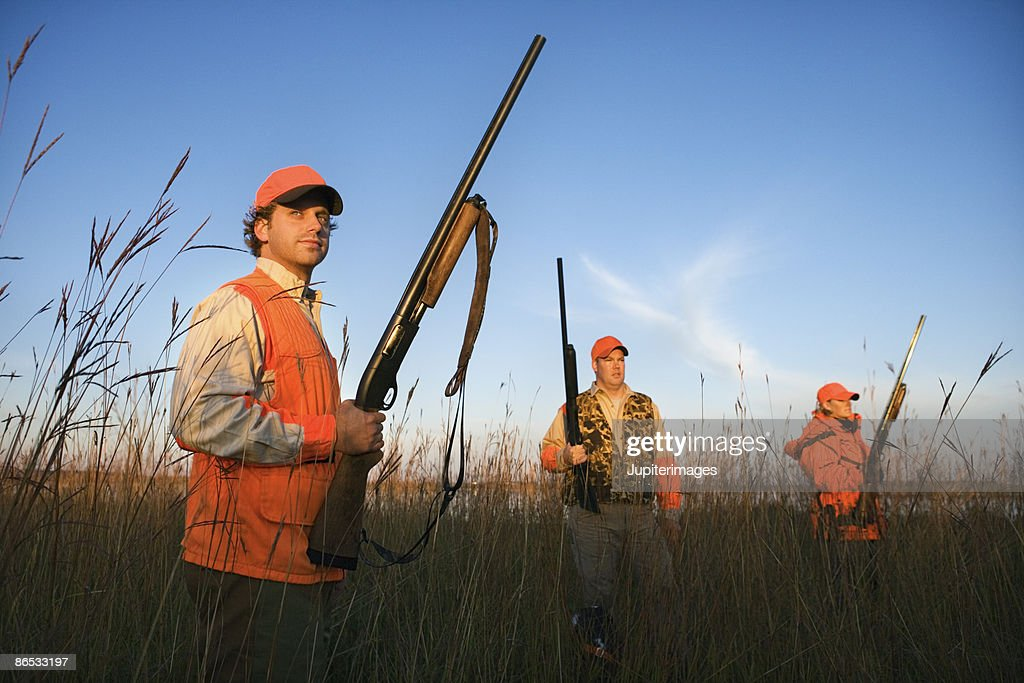 Hunters with rifles in field