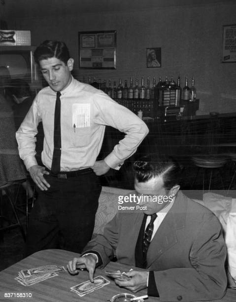 Hunting For Marked Bills Frank A Ciancio Jr watches as DA's investigator Jack Couper checks for marked bill among money taker in raid Credit Denver...