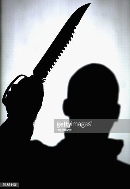 A hunting knife is held aloft by an employee at a film and television prop company December 13 2004 in London England Families of stabbing victims...
