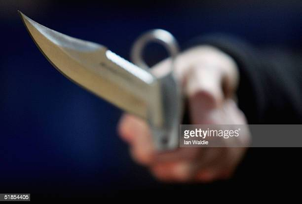 A hunting knife is held by an employee at a film and television prop company December 13 2004 in London England Families of stabbing victims have...