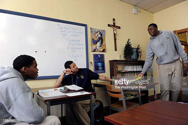 Huntington Prep senior Elijah Macon right shares his math book with senior Javontae Hawkins left and sophomore Andrew Wiggins center during class at...