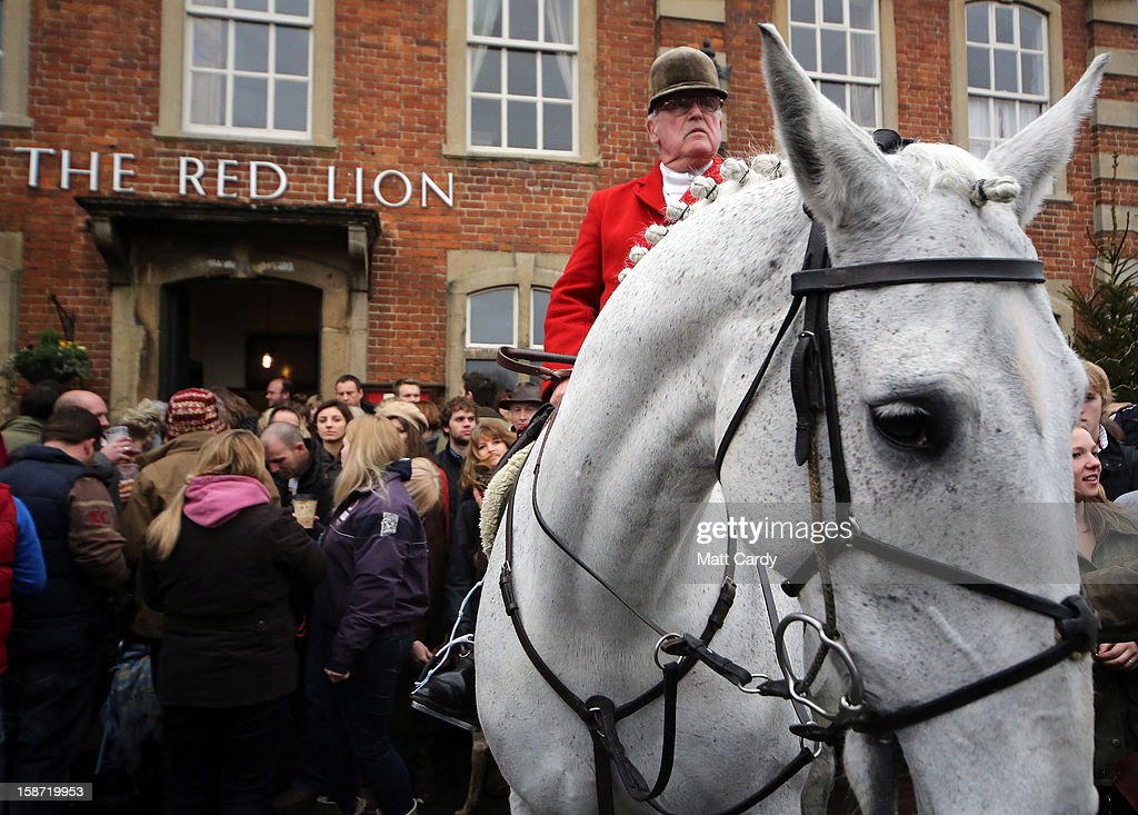 Huntsman Mike Smith from the Avon Vale Hunt, joins supporters outside the Red Lion pub who have gathered to watch their traditional Boxing Day hunt, on December 26, 2012 in Lacock, England. As hundreds of hunts met today, Environment Secretary Owen Paterson claimed that moves to repeal the ban on hunting with dogs in England and Wales may not happen in 2013, although he insisted it was still the government's intention to give MPs a free vote on lifting the ban.