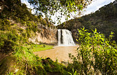 Hunua falls through lush green trees.