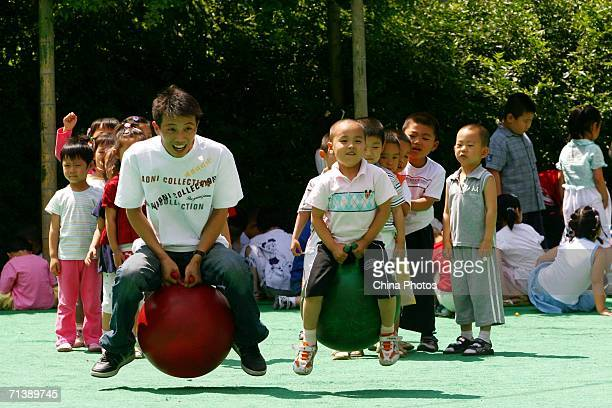 Huo Chengming a teacher at the Golden Sun Bilingual Kindergarten plays games with children on July 6 2006 in Changchun of Jilin Province China...