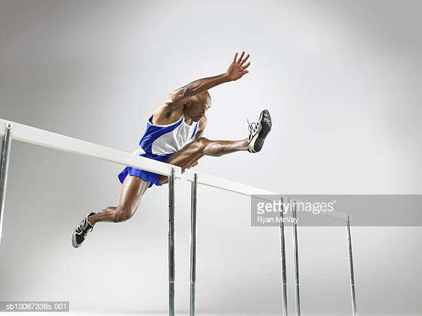 Hurdler in mid-jump (studio shot)