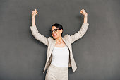 Cheerful young businesswoman in glasses gesturing and keeping her mouth open while standing against grey background