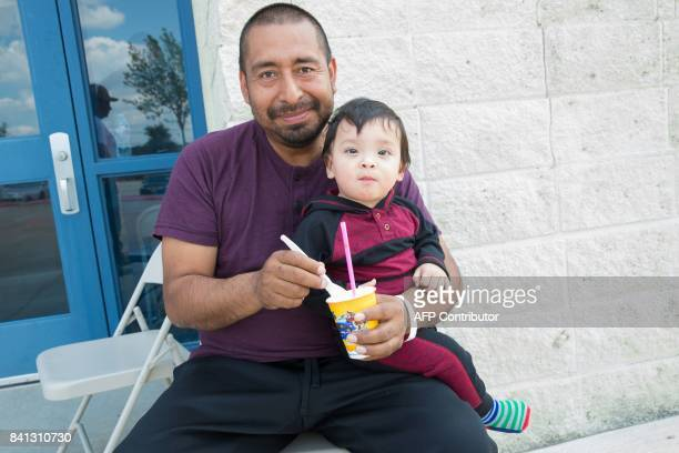 Hurricane Harvey evacuees Hector Cruz and one year old Zaiden enjoy shaved ice at the Delco Center in east Austin Texas on Thursday August 31 2017 A...