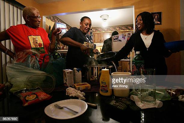 Hurricane Katrina evacuee Kathy Curry of New Orleans chats with her real estate agent Ardell Johns and Johns' mother Frieda as she prepares the...