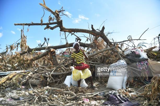 TOPSHOT A hurricane Matthew victim sits on a damaged tree after receiving food from the UN's World Food Programme in RocheaBateaux in Les Cayes in...