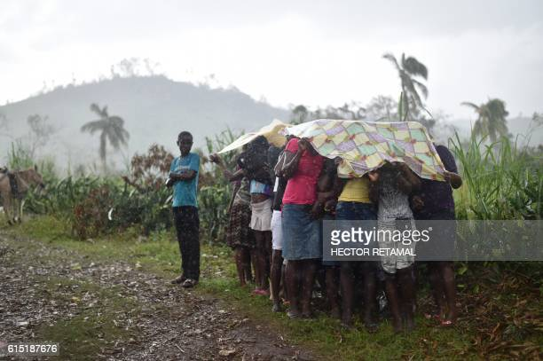 Hurricane Matthew victims cover themself from the rain while waiting for the start of delivery of food from the UN's World Food Program in the...