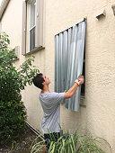 Young man installing hurricane shutters on house window, preparing for hurricane Matthew, Miramar, Florida
