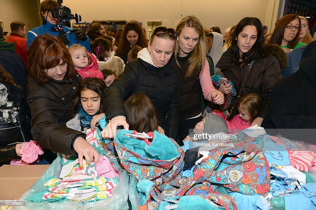 Hurricane Sandy victims look through the gifts as Heidi Klum (not pictured) teams up with friends at AOL, Patch and The American Red Cross to benefit Hurricane Sandy relief efforts at American Red Cross and Patch Sites on December 2, 2012 in Seaford, New York.