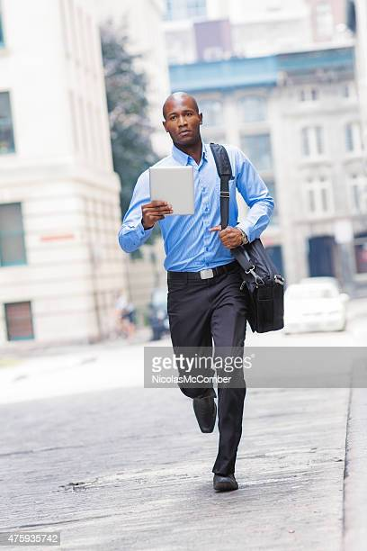 Hurried office worker running in the street tablet in hand
