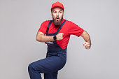 Hurry up! Young amazed handyman with beard in blue overall, red t-shirt and cap are late and starting to run for help on time. Grey background, indoor, studio shot, isolated, copy space
