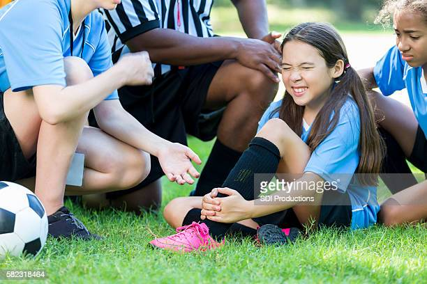 Hurt girl soccer player holding onto her ankle