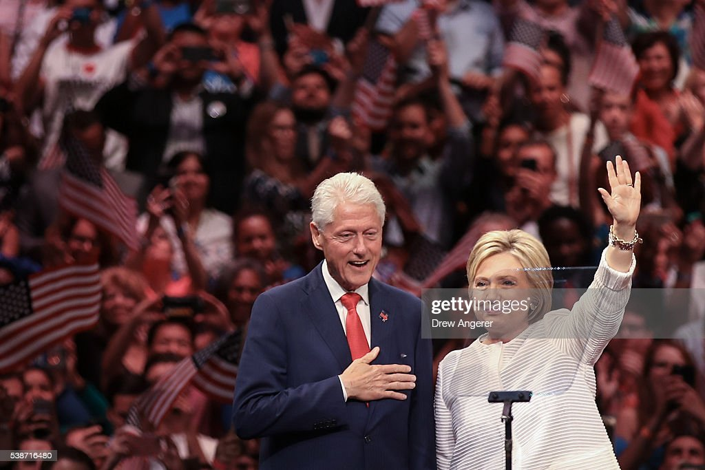 Husband and former president Bill Clinton and Democratic presidential candidate Hillary Clinton acknowledge the crowd during a primary night rally at the Duggal Greenhouse in the Brooklyn Navy Yard, June 7, 2016 in the Brooklyn borough of New York City. Clinton has secured enough delegates and commitments from superdelegates to become the Democratic Party's presumptive presidential nominee. She will become the first woman in U.S. history to secure the presidential nomination of one of the country's two major political parties.