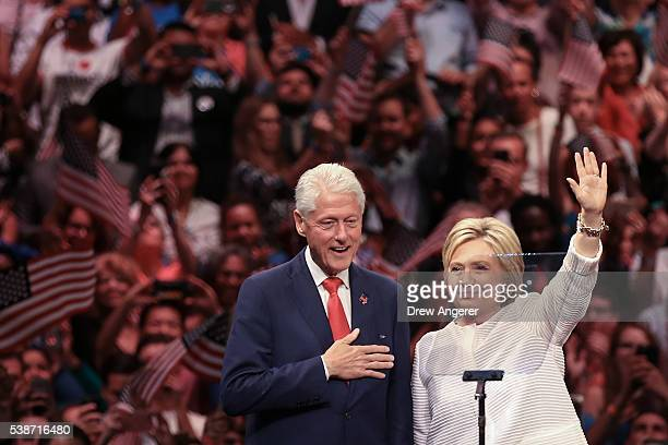 Husband and former president Bill Clinton and Democratic presidential candidate Hillary Clinton acknowledge the crowd during a primary night rally at...