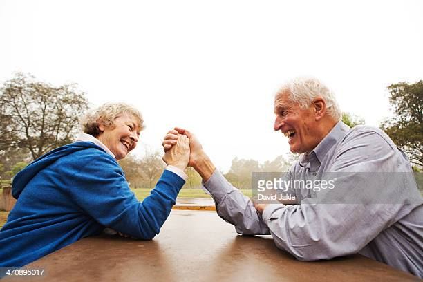 Husband and wife arm wrestling in the park