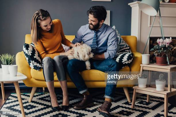 Husband and wife caressing a dog