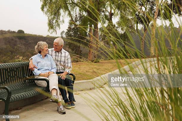 Husband and wife chatting lovingly on park bench