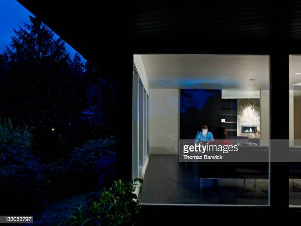 Husband and wife couple sitting in home at night