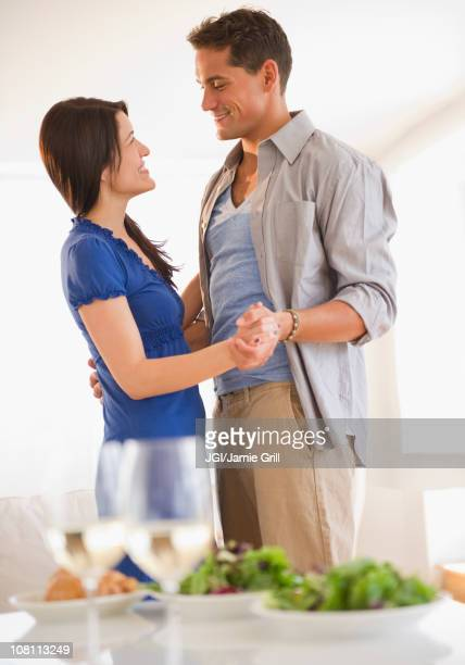 Husband and wife dancing near table set for dinner