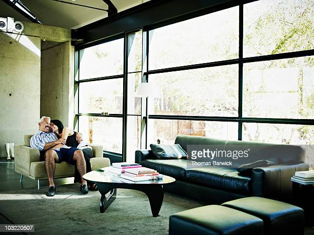 Husband and wife embracing in living room