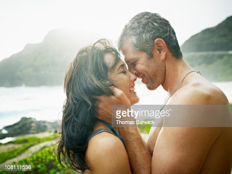 Husband and wife embracing to kiss on beach : Stock Photo