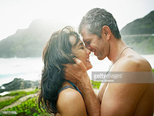 Husband and wife embracing to kiss on beach