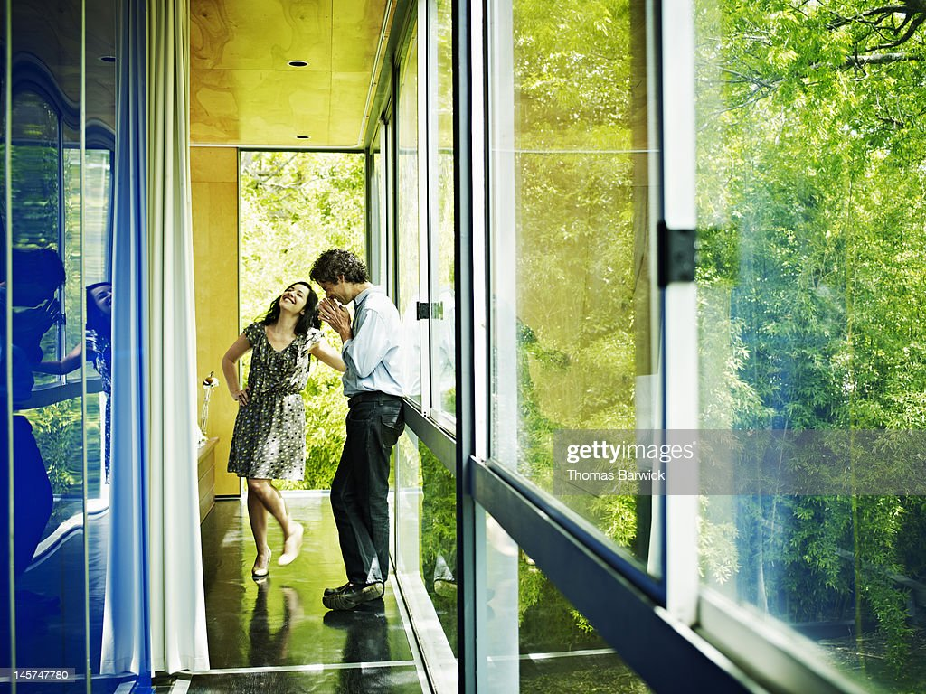 Husband and wife in bedroom of home laughing : Stock Photo