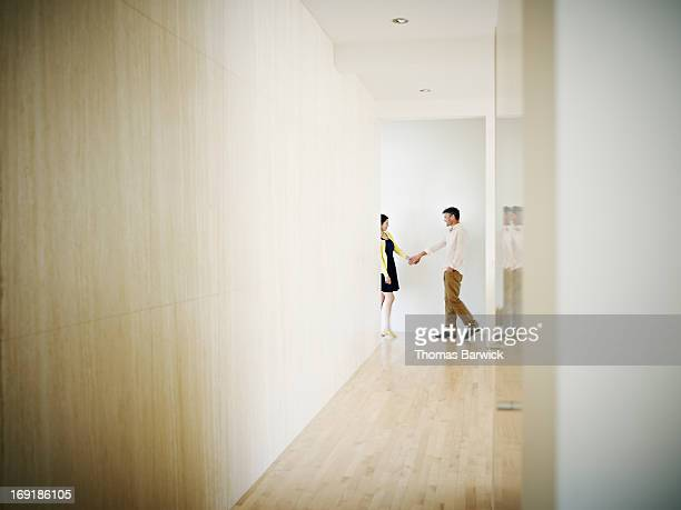 Husband and wife in hallway of modern home