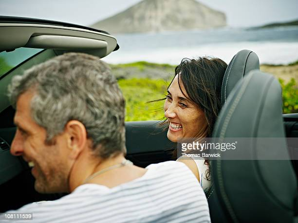 Husband and wife laughing in convertible