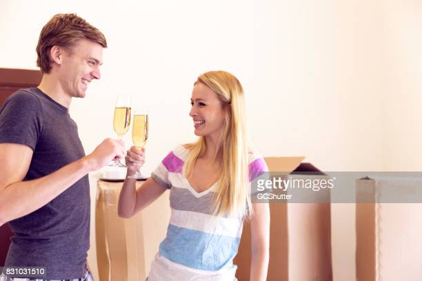 Husband and wife proposing a simple toast to themselves in celebration of their new home.