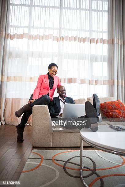 Husband and wife reading through an e-mail on couch