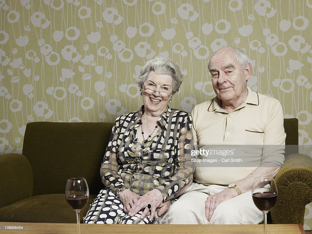 Husband and wife relaxed on sofa, with two glasses of red wine on table in front